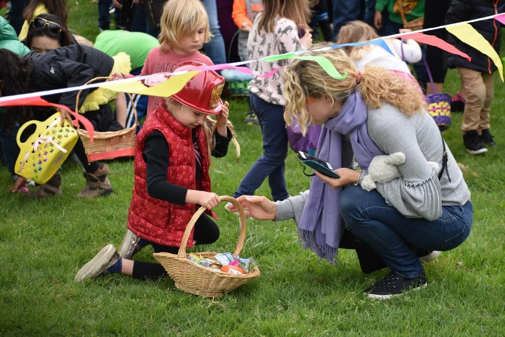 A child wearing a fireman's helmet shows an Easter basket to an adult.