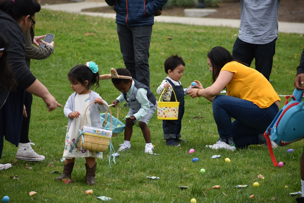 Toddlers and parents pick up Easter eggs in a field.