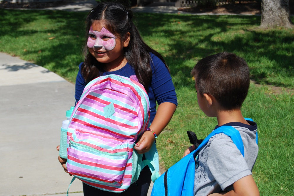 Krystabel Perez, 5, shows off her new backpack — and a colorful facepainting job.