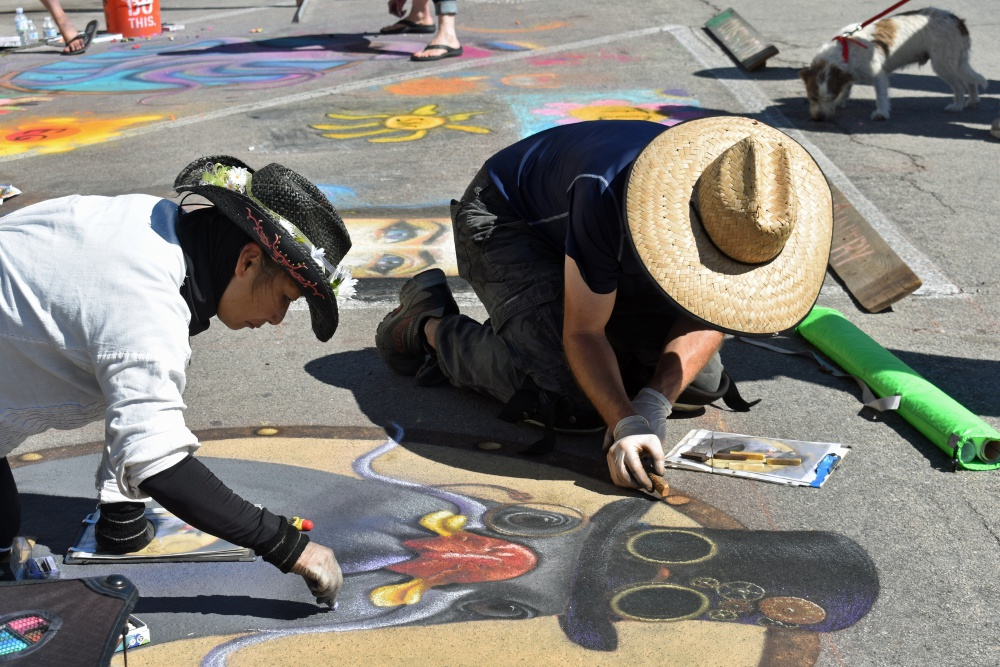Sharyn Chan, left, of Goleta, gets help working on her chalk art Saturday during the Orcutt Children's Arts Foundation Chalk Festival.