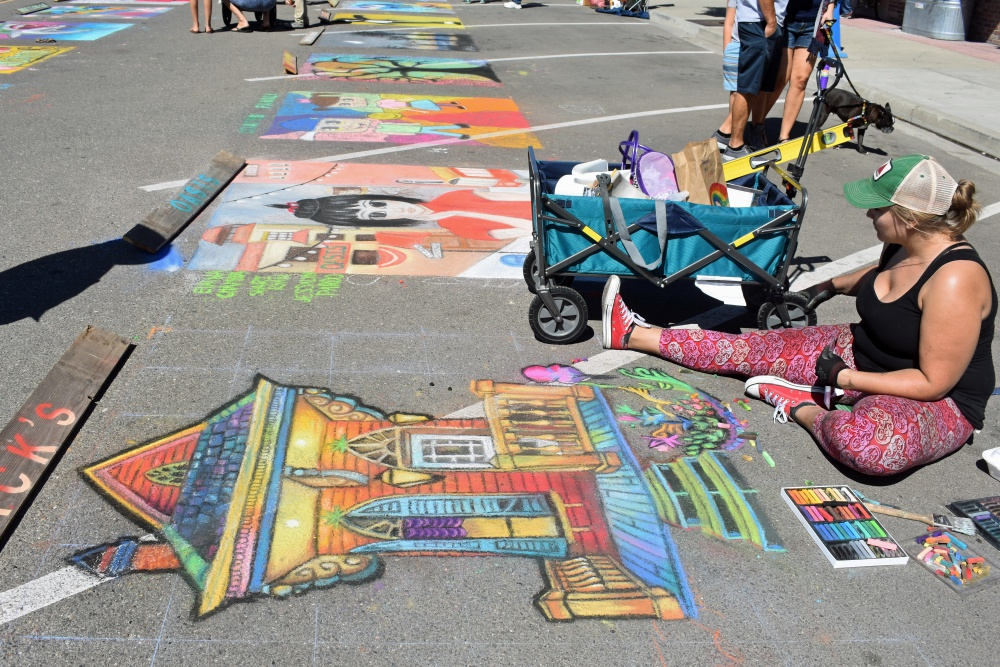 With a wagon full of supplies nearby, Pixie Thorpe works on her artwork during Orcutt Children's Arts Foundation Chalk Festival.