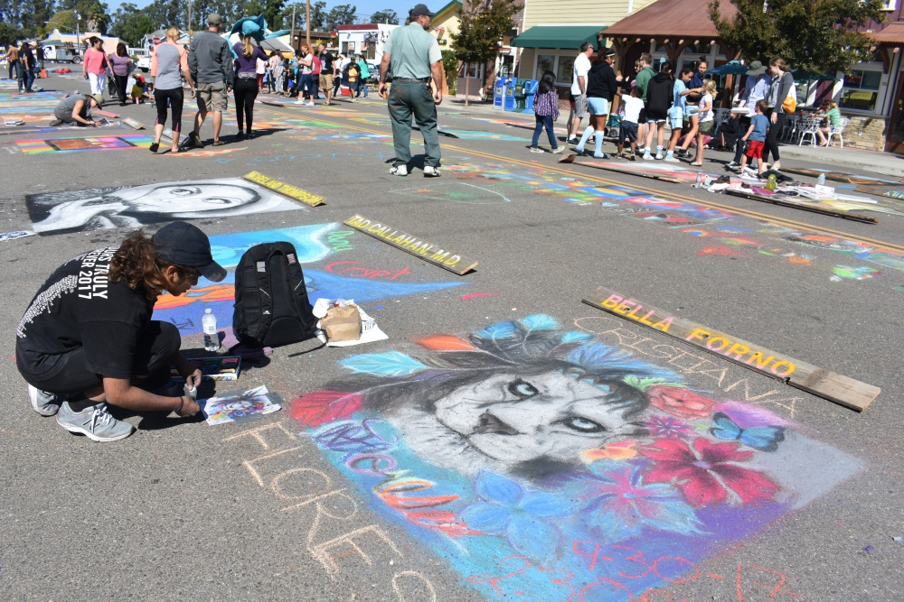 Cristina Flores tapes down the original images for her artwork during the Orcutt Children's Arts Foundation Chalk Festival on Saturday.