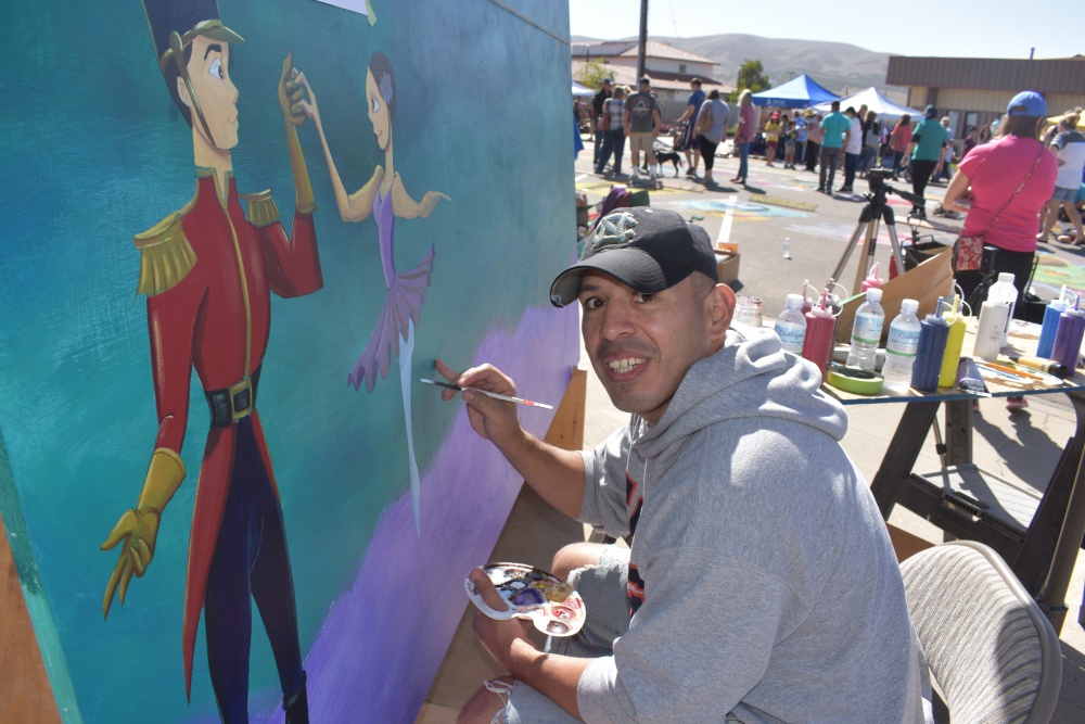 Ruben Espinoza of Orcutt works on a mural during the Orcutt Children Arts Foundation Chalk Festival on Saturday. His painting will be the subject of a raffle during the foundation's February gala.
