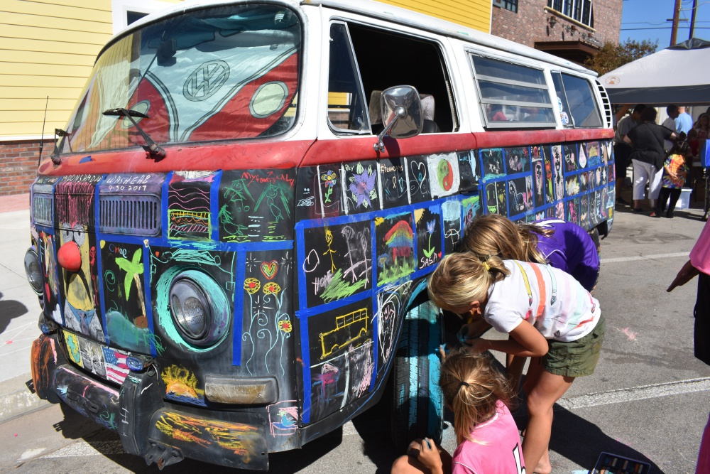 Children decorate a Volkswagen van during the Orcutt Children's Arts Foundation Chalk Festival on Saturday.