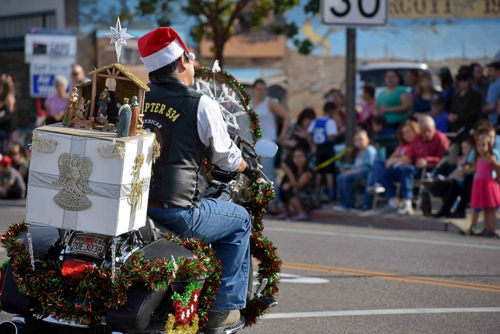 Rather than a traditional Santa Claus or stuffed bear, an American Legion rider carries a nativity scene on the back of his motorcycle Saturday during the Old Orcutt Christmas Parade.