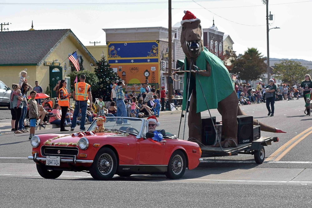 A Paradise British Car Club member tows a trailer carrying a dinosaur in the Old Orcutt Christmas Parade.
