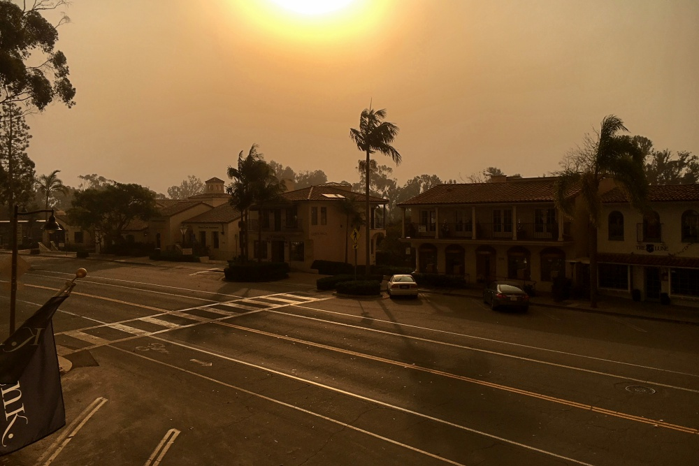 Smoke from the Thomas Fire casts an eerie haze on a deserted Coast Village Road, normally a bustling thorougfare on a Saturday morning.