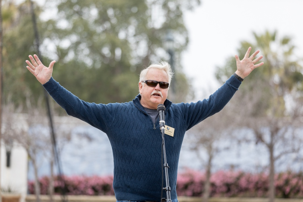 Santa Barbara City Councilman Randy Rowse waves both hands in the air while speaking into a microphone.