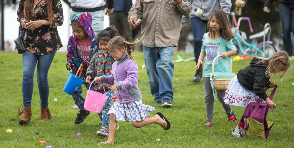 Children with Easter baskets run toward Easter eggs in a field while parents watch.