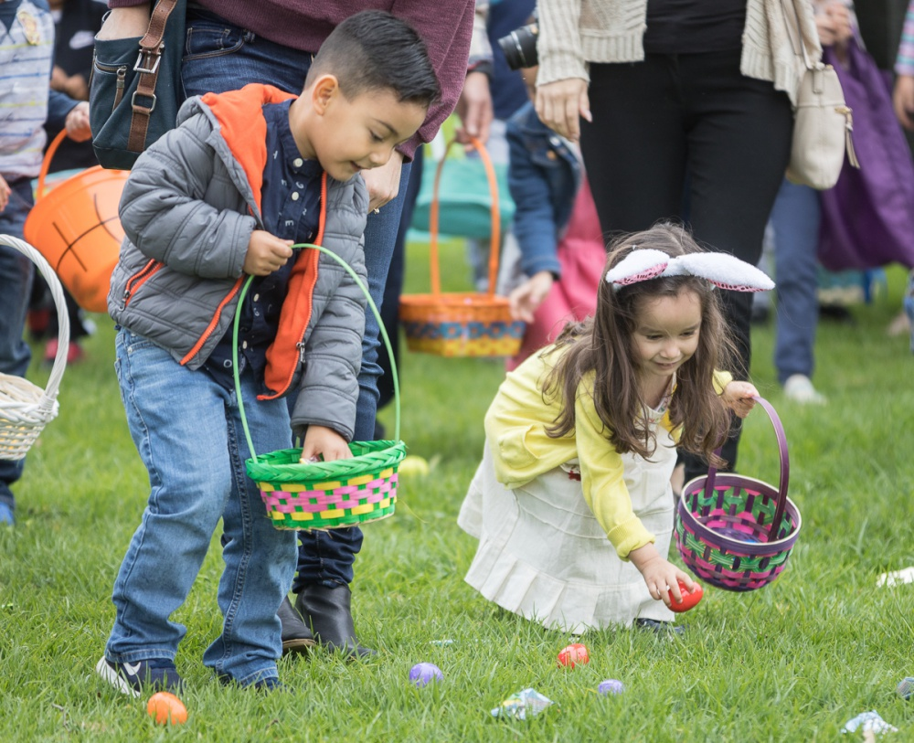 Two young children place eggs in Easter baskets.
