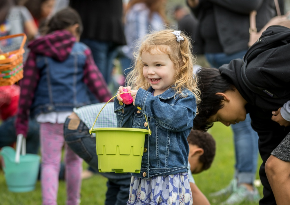 Girl smiles while placing an egg in an Easter basket.