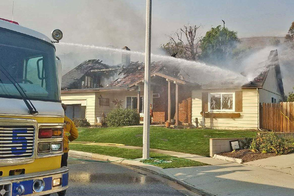 Crews hose down a fire-damaged home in the Foothill Road area of Ventura Tuesday afternoon.