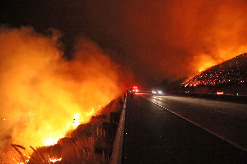 Flames from the Thomas Fire were burning on both sides of Highway 101 west of Ventura Tuesday night.