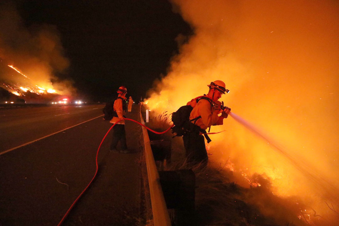 A firefighter aims a hose line at flames from the Thomas Fire burning along Highway 101 west of Ventura.