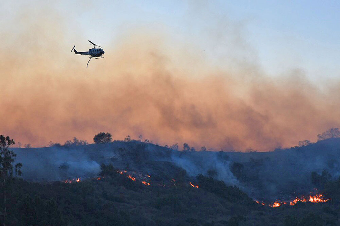 A helicopter prepares to make a water drop on the Thomas Fire