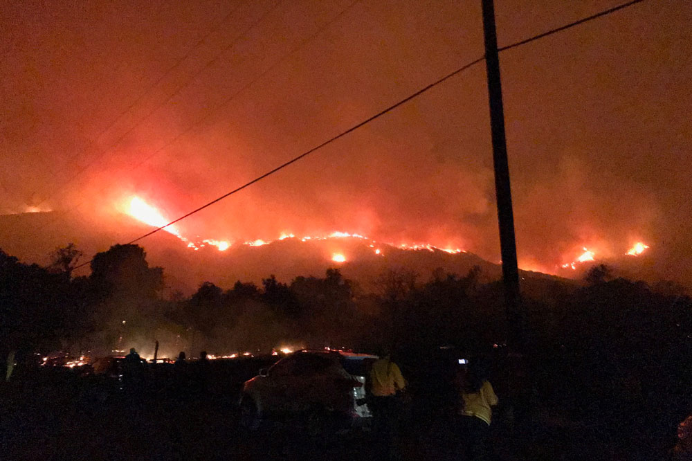 Flames line the ridgeline north of Highway 150 near Lake Casitas Saturday night. Firefighters conducted firing operations in the area earlier, but the flames continued to spread.