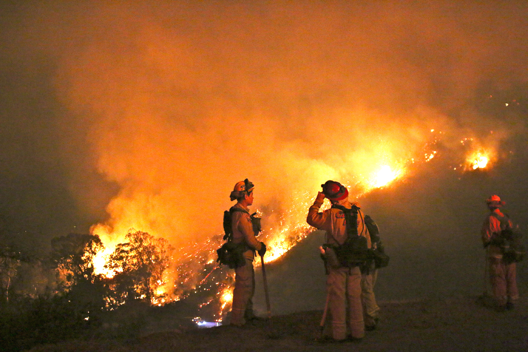Firefighters on Bella Vista Drive watch the Thomas Fire burn in Romero Canyon Tuesday night.