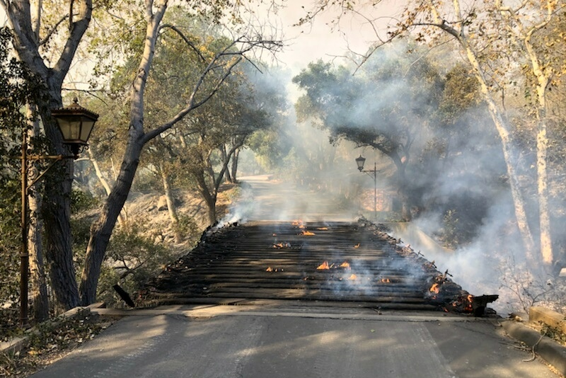A private driveway bridge smolders after the Thomas Fire blew through the Hot Springs Road property early Saturday.