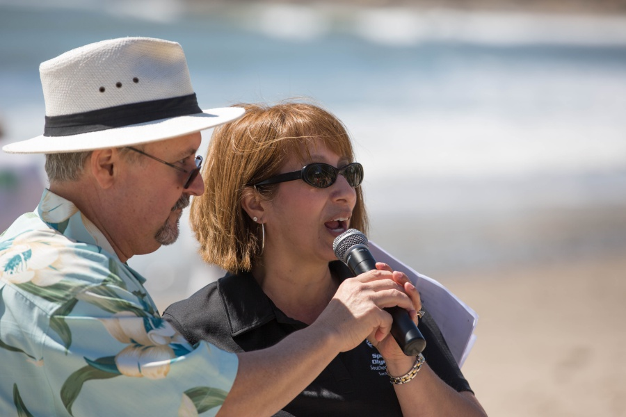 Polar Plunge emcee Drew Wakefield turns the microphone over to Gina Carbajal, regional director of Special Olympics Santa Barbara.
