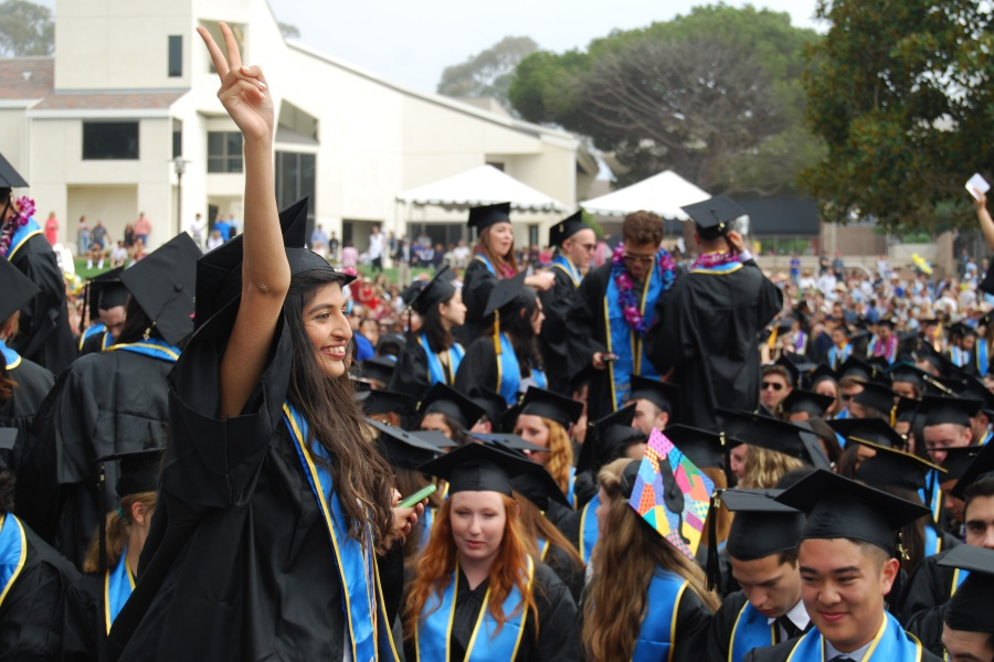 A soon-to-graduate UC Santa Barbara student waves to family and friends at Saturday's commencement ceremony at the Faculty Club lawn.