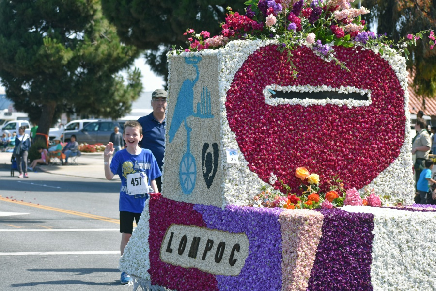 A boy waves to the crowd while walking behind the Odd Fellows float in the Lompoc Valley Flower Festival Parade.