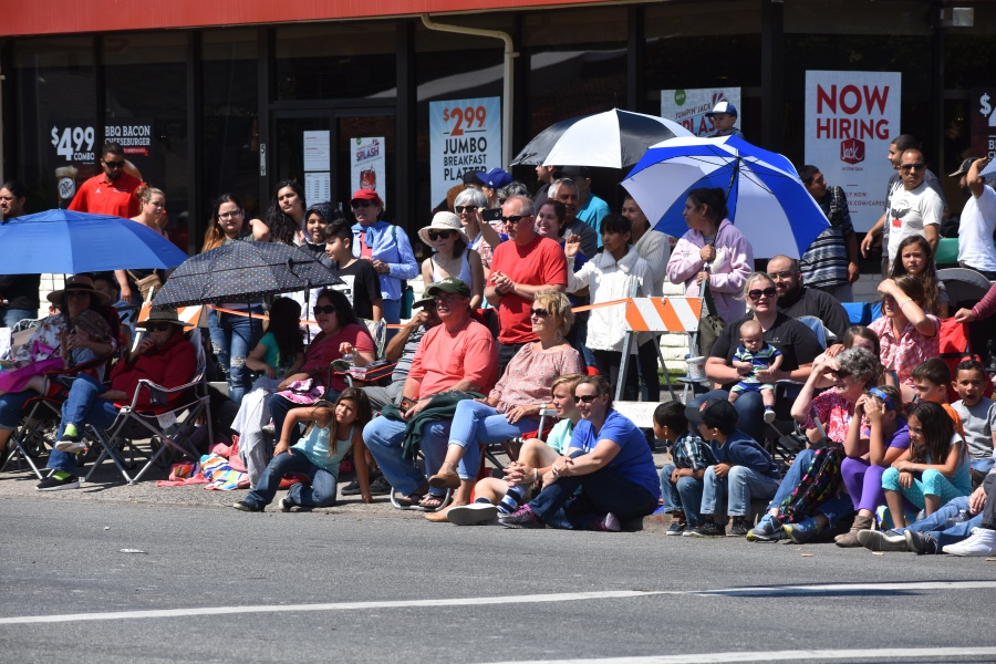 Lompoc Valley residents lining the Flower Festival Parade route use umbrellas to provide shade from the sun.