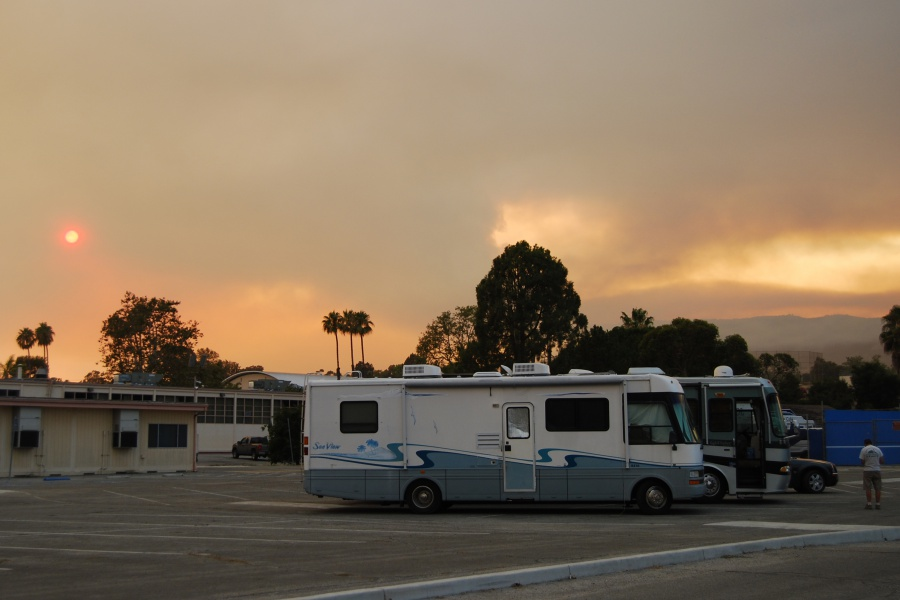 With the setting sun obscured by smoke from the Whittier Fire, RVs of evacuees line the parking lot at San Marcos High School, where an emergency shelter has been established.