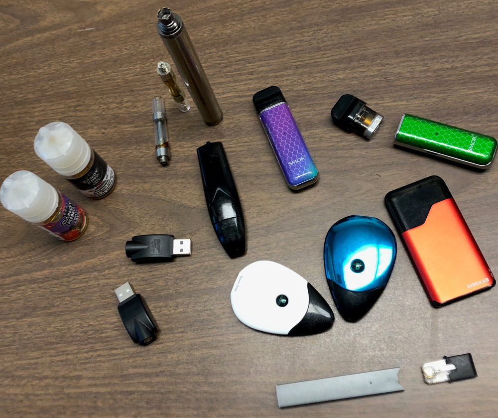 Assortment of e-cigarettes, chargers and e-juice
