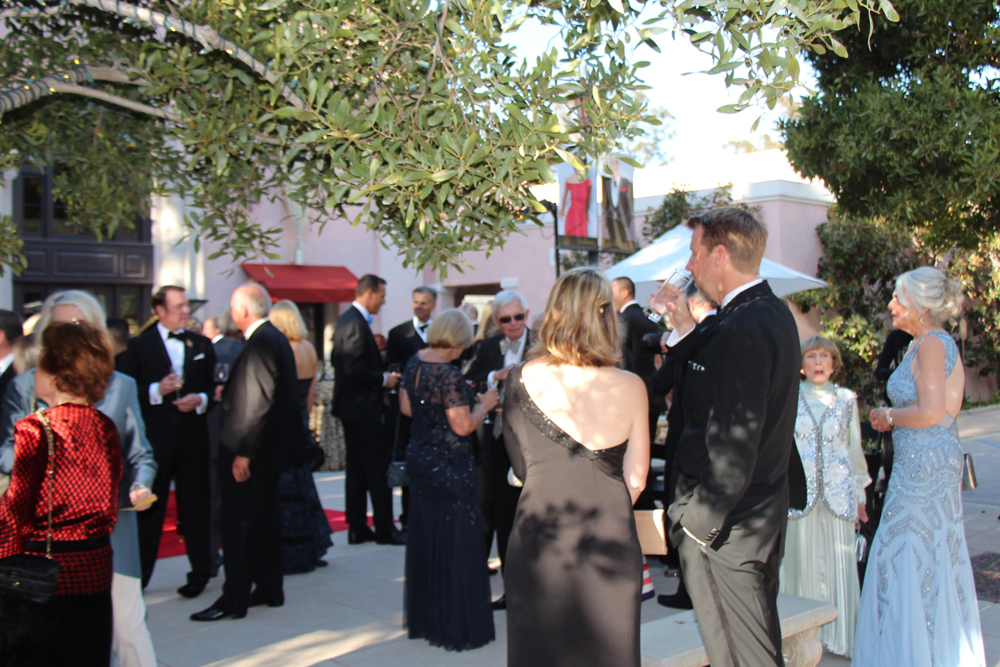 Guests mingle under oak trees during the welcome reception on the patio adjacent to Hahn Hall.