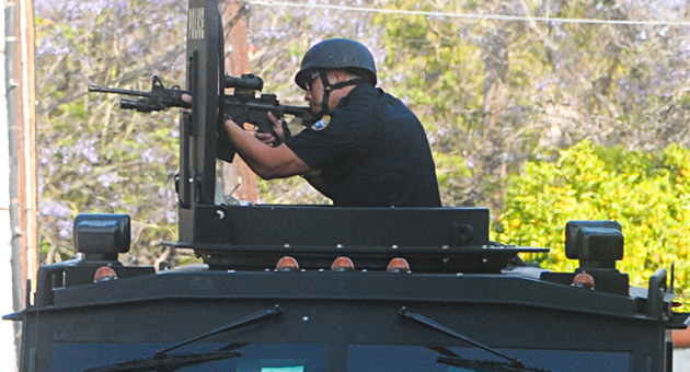 A Santa Barbara police officer, responding to shots being fired on San Pascual Street, emerges from an armored vehicle and trains a gun at a window of the El Carrillo Apartments on Saturday. (Lara Cooper / Noozhawk photo)
