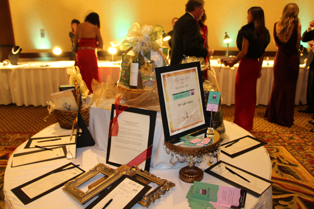 Guests survey an array of silent auction items.