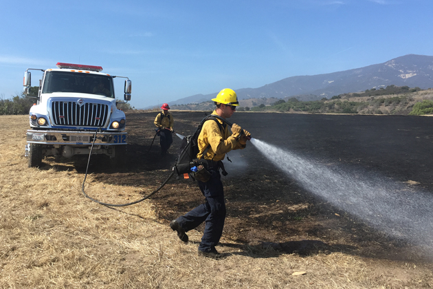 Fire crews extinguish smoldering grass after a 2-acre fire near Dos Pueblos Canyon west of Goleta Monday afternoon.